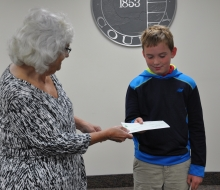 Toni Drier looks on as Melinda Spencley presents Jack Robinson with check for first place award of $100.