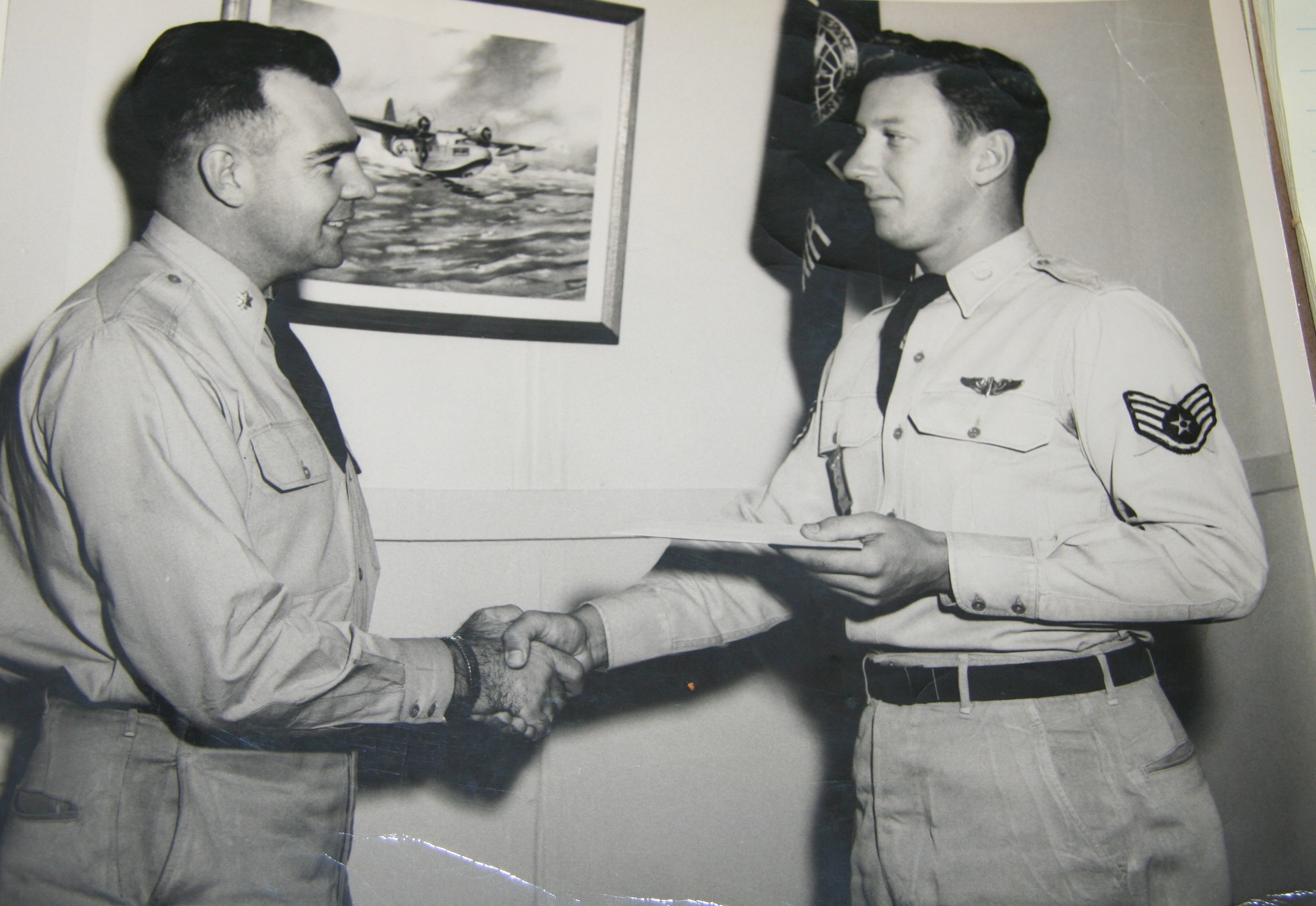 In 1952, Technical Sergeant Bill Steffens (right) is congratulated by the Commanding Officer of his squadron at Hickam Air Force Base in Owahu, Hawaii, for his winning design of a logo for the then Air Sea Rescue Unit.