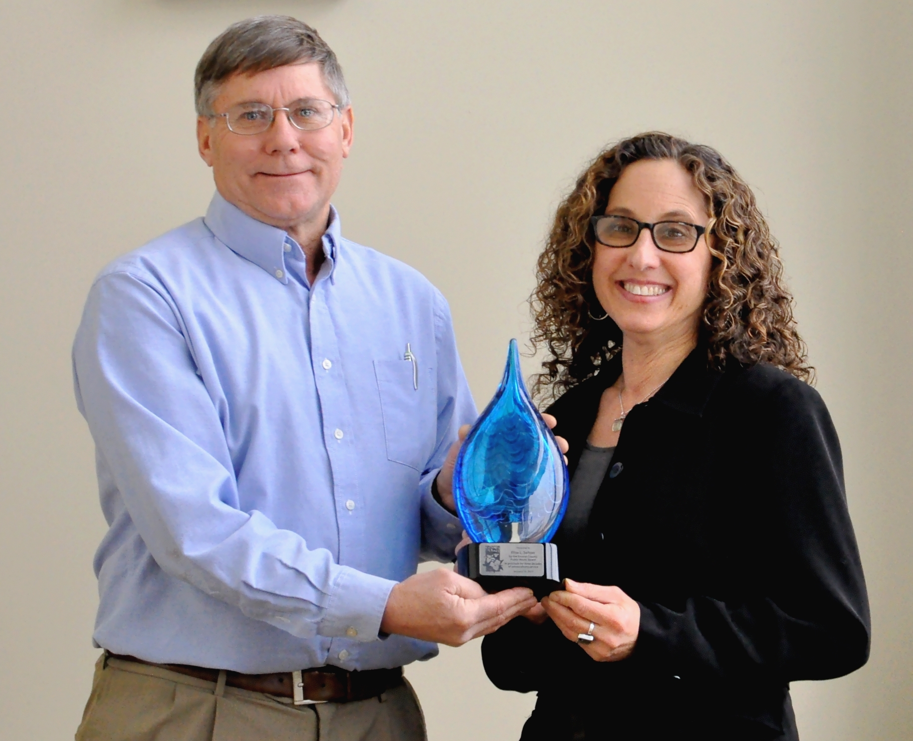 Photo of Denny Keiser presenting sculpture to Elisa at January DPW Board Meeting
